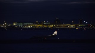 AX128_119 - 6K stock footage aerial video track taxiing private jet at SLC Airport at night in winter, Utah
