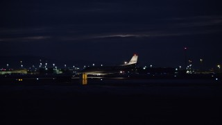 AX128_120 - 6K stock footage aerial video track private jet taxiing off runway at night in winter, Salt Lake City International Airport, Utah