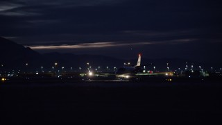 AX128_121 - 6K stock footage aerial video track private jet taxiing off SLC Airport runway at night in wintertime, Utah