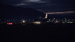 AX128_122 - 6K stock footage aerial video of tracking a private jet taxiing at SLC Airport at night in winter, Utah