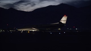 AX128_123 - 6K stock footage aerial video track a private jet as it taxis by at SLC Airport at night in winter, Utah