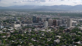 AX129_060 - 6K stock footage aerial video of flying by city buildings, distant Oquirrh Mountains, Downtown Salt Lake City, Utah