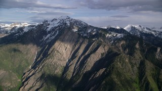 AX129_100 - 6K stock footage aerial video of approaching the snow-capped peaks of the Wasatch Range, Utah