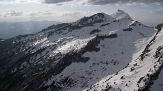 AX129_120 - 6K stock footage aerial video of flying by Lone Peak, snow-covered Wasatch Range, Utah