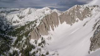 AX129_125 - 6K stock footage aerial video of passing white slopes of Lone Peak in the snowy Wasatch Range, Utah