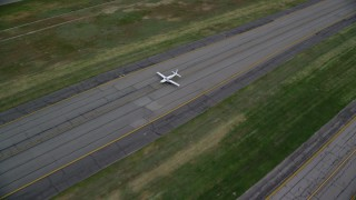 AX130_002 - 6K stock footage aerial video of flying away from a taxiing airplane, Salt Lake City International Airport, Utah