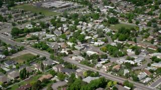 AX130_021 - 6K stock footage aerial video of approaching suburban neighborhood, tilt to rooftops, West Jordan, Utah