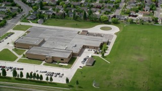 AX130_026 - 6K stock footage aerial video of orbiting West Hills Middle School and grass fields, West Jordan, Utah