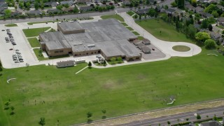 AX130_027 - 6K stock footage aerial video of flying away from West Hills Middle School and grass fields, West Jordan, Utah