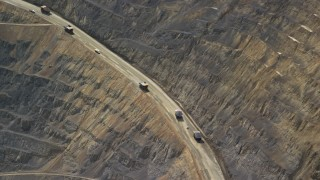 AX130_043 - 6K stock footage aerial video of flying by gravel haulers, Kennecott Copper Mine, Bingham Canyon Mine, Utah