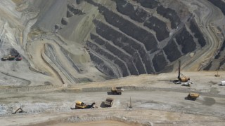 AX130_050 - 6K stock footage aerial video of orbiting around gravel haulers, Kennecott Copper Mine, Bingham Canyon Mine, Utah