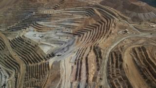 AX130_056 - 6K stock footage aerial video of reverse view of gravel haulers, Bingham Canyon Mine, Utah