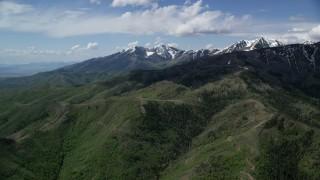 AX130_059 - 6K stock footage aerial video of flying toward snowy peaks beyond green ridges, Oquirrh Mountains, Utah