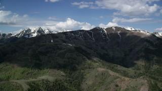 AX130_060 - 6K stock footage aerial video of flying by snowy peaks, green ridges, Oquirrh Mountains, Utah