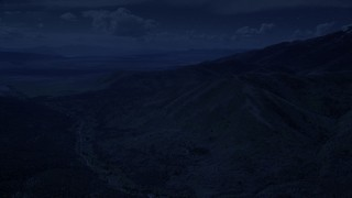 AX130_064_DFN - Aerial stock footage of 4K day for night color corrected aerial footage of approaching rugged mountain ridges, Oquirrh Mountains, Utah