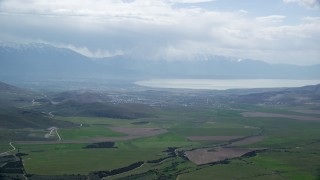 AX130_069 - 6K stock footage aerial video of passing by green farmland, Utah Lake, Utah