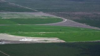 AX130_078 - 6K stock footage aerial video of flying by circular crop fields, tractors, Cedar Fort, Utah