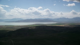 AX130_080 - 6K stock footage aerial video of flying by farmland, distant mountain range and Utah Lake, Utah