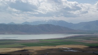 AX130_082 - 6K stock footage aerial video of flying by circular crop fields, distant snow-capped peak and Utah Lake, Utah