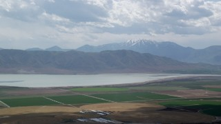 AX130_083 - 6K stock footage aerial video of a view of circular crop fields, distant snow-capped peak and Utah Lake, Utah