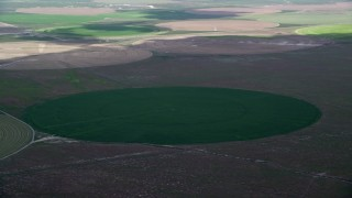 AX130_085 - 6K stock footage aerial video of passing by green circular crop fields, Elberta, Utah