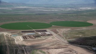 AX130_090 - 6K stock footage aerial video flyby two green circular crop fields, Elberta, Utah