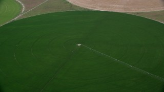 AX130_092 - 6K stock footage aerial video of approaching circular crop field, tilt to irrigation system, Elberta, Utah