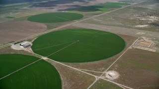 AX130_093 - 6K stock footage aerial video of approaching circular crop fields and tilt to one of them, Elberta, Utah