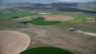 AX130_098 - 6K stock footage aerial video of flying over and approaching circular crop fields, silos, Elberta, Utah