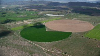 AX130_099 - 6K stock footage aerial video of approaching Pac-man shaped circular crop field, Elberta, Utah