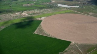 AX130_100 - 6K stock footage aerial video of passing by Pac-man shaped and circular crop fields, Elberta, Utah