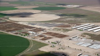 AX130_101 - 6K stock footage aerial video of flying by circular crop fields, greenhouses, ponds, Elberta, Utah