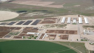 AX130_102 - 6K stock footage aerial video of passing by greenhouses, ponds, near circular crop fields, Elberta, Utah