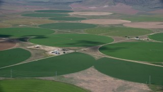 AX130_104 - 6K stock footage aerial video of flying by large field of circular crop fields, Elberta, Utah