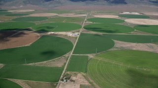 AX130_106 - 6K stock footage aerial video of passing large circular crop fields, Elberta, Utah