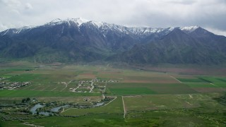 AX130_113 - 6K stock footage aerial video of flying by Burraston Ponds, small rural town, Wasatch Range, Mona, Utah