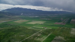 AX130_115 - 6K stock footage aerial video of approaching small rural town, farmland, Nephi Municipal Airport, Nephi, Utah