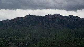 AX130_121 - 6K stock footage aerial video of flying by a peak in the Wasatch Range, Salt Creek Peak, Utah