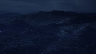 AX130_132_DFN - Aerial stock footage of 4K day for night color corrected aerial footage of flying by shadowy mountains, trees, Wasatch Range, Utah