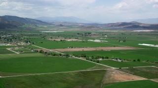 AX130_143 - 6K stock footage aerial video of approaching farmland, rural roads, distant mountain ranges, Manti, Utah