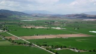 AX130_144 - 6K stock footage aerial video of approaching farmland, distant mountain ranges, Manti, Utah