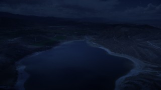 AX130_154_DFN - Aerial stock footage of 4K day for night color corrected aerial footage fly over the Gunnison Reservoir, low water, approach farms, Sterling, Utah