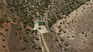 AX130_155 - 6K stock footage aerial video approach and tilt to isolated home, dry hills, Sterling, Utah