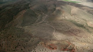 AX130_156 - 6K stock footage video of flying over dirt roads, dry hills, Sterling, Utah