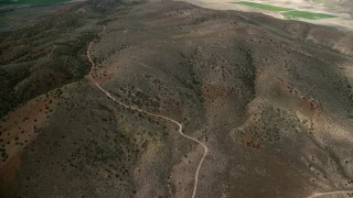 AX130_157 - 6K stock footage aerial video of flying over dirt roads in dry hills, Sterling, Utah