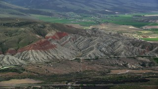 AX130_158 - 6K stock footage aerial video of flying by rugged hills, farmland in background, Sterling, Utah