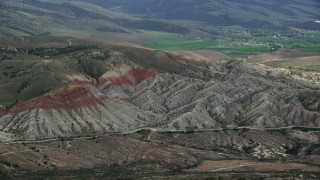 AX130_159 - 6K stock footage aerial video of flying by hills, farmland in the background, Sterling, Utah