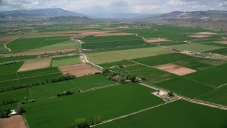 AX130_164 - 6K stock footage aerial video of flying over farmland, rural roads, Aurora, Utah