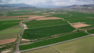 AX130_165 - 6K stock footage aerial video fly over farmland, roads separating fields, Aurora, Utah