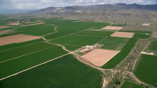 AX130_166 - 6K stock footage aerial video of flying by farmland and a barn, Aurora, Utah